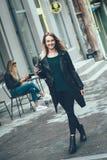 美好的年轻时髦的偶然女服以黑时尚给走和拿着黑咖啡穿衣,享用,微笑 免版税库存图片
