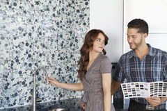 美好的年轻有颜色样品的夫妇站立的样房厨房 库存图片