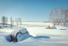 美好的晴朗的冬天风景 干草劳斯在雪的 免版税库存照片