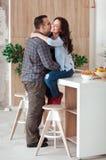 美好的年轻热情的夫妇是微笑和拥抱在家以前有性在厨房 免版税图库摄影