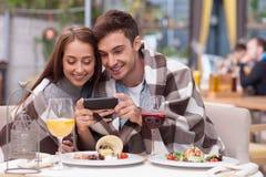 美好的年轻爱恋的夫妇使用电话 库存图片