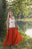 美好的年轻白肤金发的妇女跳舞在河岸的森林里 免版税图库摄影