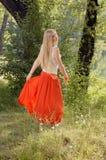 美好的年轻白肤金发的妇女跳舞在河岸的森林里 库存图片