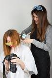 美好的年轻腿长的红发模型看在照相机,美发师的图片做发型 女孩玻璃二 免版税图库摄影