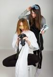 美好的年轻腿长的红发模型看在照相机,美发师的图片做发型 女孩玻璃二 图库摄影