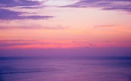 美好的紫色在海的日落灼烧的天空 免版税库存图片
