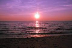 美好的紫色在海的日落灼烧的天空 库存图片