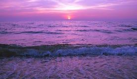 美好的紫色在海的日落灼烧的天空 免版税图库摄影
