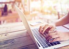 美好的年轻行家妇女` s递繁忙研究她的坐在咖啡店的木桌上的膝上型计算机 库存图片
