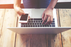 美好的年轻行家妇女` s递繁忙研究她的膝上型计算机,女性使用坐在木桌上的手机 免版税图库摄影