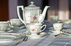美好的porcelaine杯子、水罐和银利器在桌上 库存照片