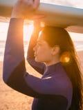 年轻美好的surfgirl与长的头发和在保温潜水服 摆在与在海洋附近的水橇板日落的 为冲浪准备 库存图片