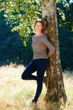 美好老妇人微笑的倾斜反对树 免版税库存图片