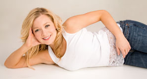 美好金发碧眼的女人躺下的放松的微笑 免版税图库摄影