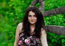 美好震惊,有完善的面孔的精妙,逗人喜爱的女孩,有黑发立场的深色的女孩在木篱芭附近户外在森林里 免版税库存图片