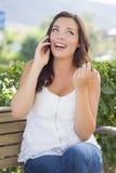 美好青少年女性谈话在手机户外在长凳 免版税库存照片