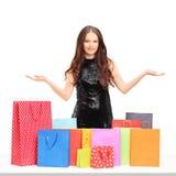 美好年轻女性摆在与五颜六色的购物袋 免版税库存图片
