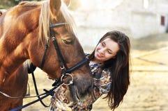 美好年轻女性走和爱抚她的棕色马在乡下 免版税库存图片