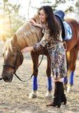美好年轻女性走和爱抚她的棕色马在乡下 免版税库存照片