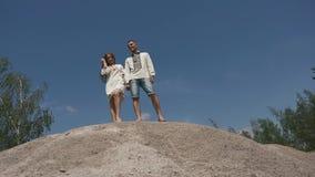 美好enloved对摆在室外在湖岸在乌克兰传统衣物 跑在岩石的年轻夫妇 影视素材