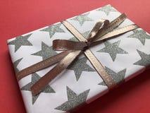 美妙地包裹了在简单的红色背景的圣诞礼物 免版税库存照片