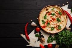 美妙地服务的hummus顶视图  辣在木背景的hummus用胡椒和绿色板材  复制空间 免版税库存图片