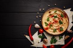 美妙地服务的hummus顶视图  辣在木背景的hummus用胡椒和绿色板材  复制空间 库存图片