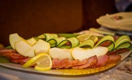 美妙地被切的苹果切片、烟肉和黄瓜 免版税库存图片