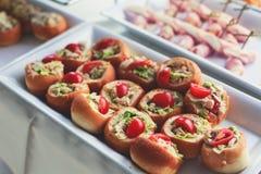 美妙地装饰的承办的宴会桌以不同的食物快餐和开胃菜品种在公司圣诞节生日 库存照片