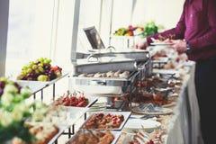 美妙地装饰的承办的宴会桌以不同的食物快餐和开胃菜品种在公司圣诞节生日 免版税库存图片