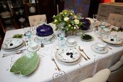 美妙地装饰的桌设置了与花、蜡烛、板材和餐巾婚姻或另一个事件的在 免版税库存图片