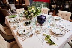 美妙地装饰的桌设置了与花、蜡烛、板材和餐巾婚姻或另一个事件的在 免版税图库摄影