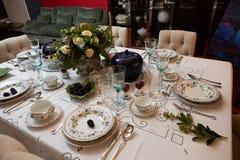 美妙地装饰的桌设置了与花、蜡烛、板材和餐巾婚姻或另一个事件的在 图库摄影