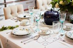 美妙地装饰的桌设置了与花、蜡烛、板材和餐巾婚姻或另一个事件的在 免版税库存照片