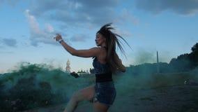 美妙地跳舞在angoo跃迁鞋子的年轻女人,在绿色烟 r 影视素材