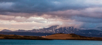 美妙的冰岛自然风景 高山、雪、山riwer和绿色草原 免版税库存图片