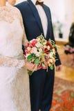 美妙的婚礼花束的侧视图在新娘的手上 免版税图库摄影