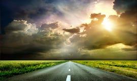 美妙的日落和一条被铺的路通过领域和草甸 库存图片