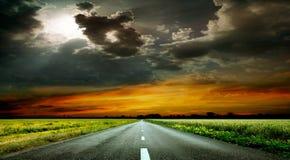 美妙的日落和一条被铺的路 免版税库存图片