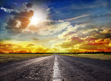 美妙的日落和一条被铺的路 图库摄影