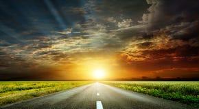 美妙的日落和一条被铺的路 免版税库存照片