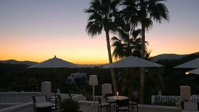 美妙的日落在有棕榈、伞和蜡烛的豪华旅馆里 在温泉渡假胜地的放松 完善的休息 影视素材