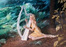 美妙的森林矮子在树和戏剧下坐白色竖琴,有在长的黄色礼服编辫子的长的金发的女孩 免版税图库摄影