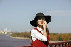 美妙的模型特写镜头画象穿红色服装,黑帽会议 库存图片