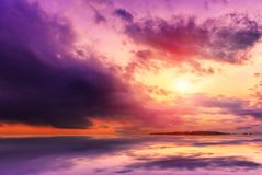 美妙的横向 在湖,光芒的剧烈的场面日落通过在水反映的重的暴风云喷发 免版税库存图片