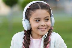 美妙的生活 愉快的女孩穿戴耳机 少许音乐迷 小孩听到室外的音乐 愉快小 免版税图库摄影