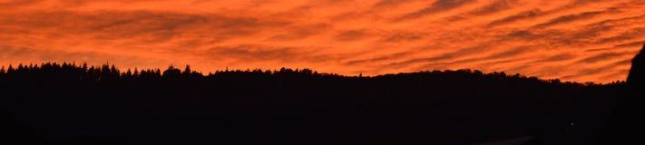 美妙的风景在天结束时 在山土坎的日落 与明亮的红色血液颜色的美好的风景 免版税库存图片