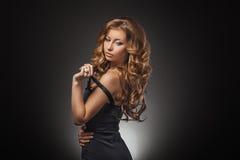美妙的年轻白肤金发的妇女画象有看照相机的长的头发的 性感蓝色黑暗的礼服的女孩 免版税库存图片