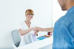 美容师与他的男性客户握手在诊所的招待会 库存图片