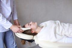 美容师人做特别面孔按摩给有cosmet的女孩 图库摄影